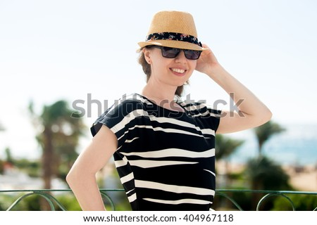 Portrait of friendly smiling young woman in sunglasses and summer dress standing on the balcony with sea view, holding her straw hat from breeze - stock photo