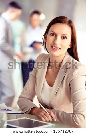 Portrait of friendly specialist looking at camera on the background of working colleagues