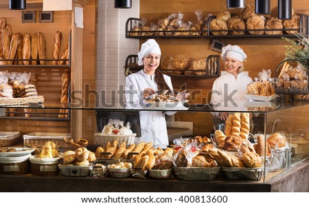 Portrait of friendly women at a bakery display with a pastry. Focus on young women  - stock photo