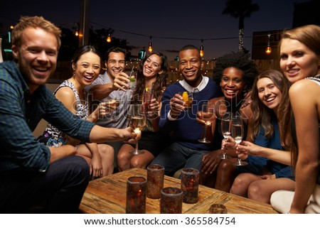 Portrait Of Friends Enjoying Night Out At Rooftop Bar - stock photo