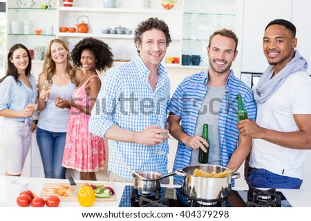 Portrait of friends holding beer bottles and glasses of wine in kitchen at home - stock photo