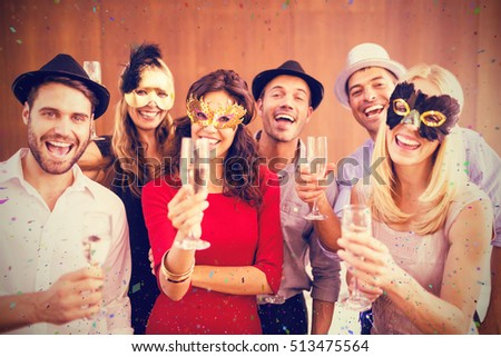 Portrait of friends holding champagne flute while standing together against flying colours