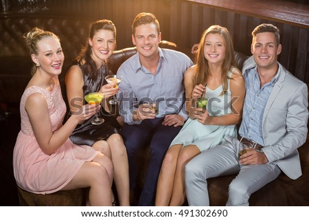 Portrait of friends holding glasses of cocktail in bar