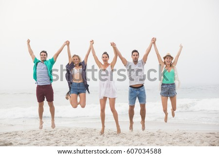 Portrait of friends holding hands and jumping in a row on the beach