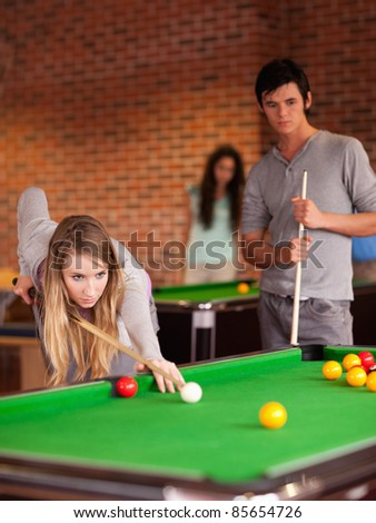 Portrait of friends playing snooker in a student home - stock photo
