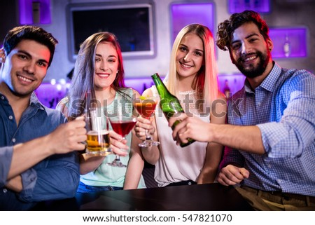 Portrait of friends toasting cocktail, beer bottle and beer glass at bar counter in bar
