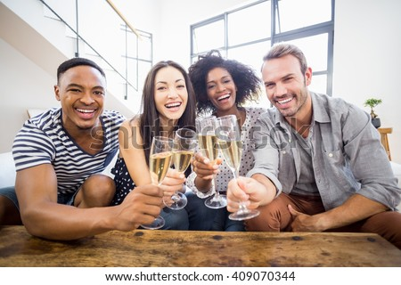 Portrait of friends toasting glasses of champagne in living room - stock photo