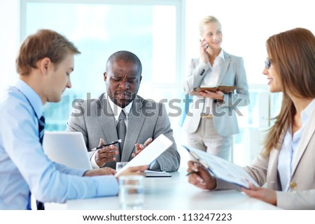 Portrait of frowning boss looking at document with his two employees sitting near by