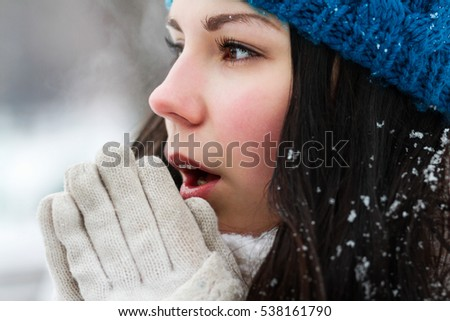 Portrait of frozen white brunette girl in knit blue hat.Young woman breathe with warm air on her frozen hands.Close up.Pretty female model outside in cold winter day.Cute European chick freezing