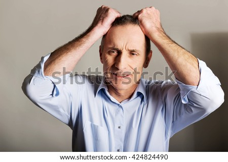 Portrait of frustrated man pulling his hair  - stock photo