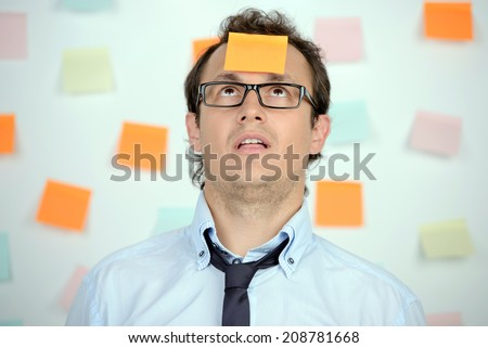 Portrait of frustrated young man in formalwear and adhesive note on his forehead standing against the wall with many adhesive notes on it - stock photo