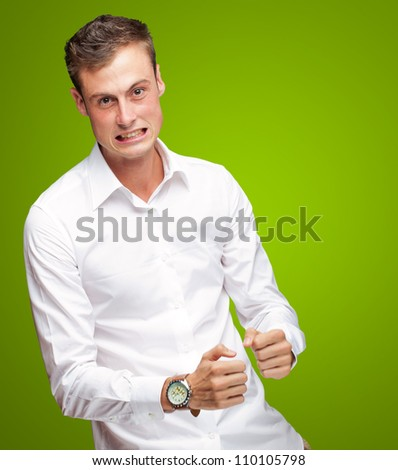 Portrait Of  Frustrated Young Man On Green Background