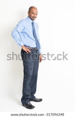Portrait of full body mature Indian business man with blue shirt standing on plain background.