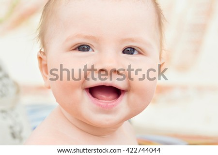Portrait of funny baby sitting on sun, outdoor shot