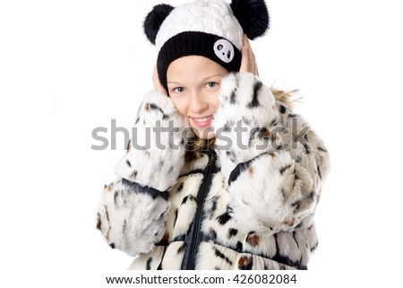 Portrait of funny beautiful casual caucasian teenage girl wearing cozy white winter coat and knitted hat, hiding her ears and cheeks from cold, studio image, white background - stock photo
