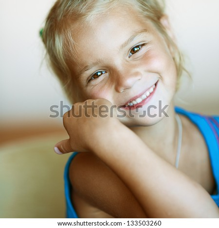 Portrait of funny beautiful little girl close-up, sitting on table. - stock photo