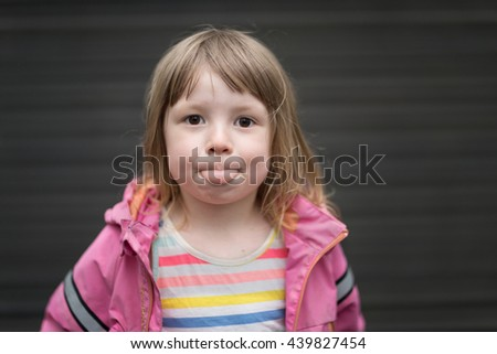 portrait of funny blond girl in preschool age wearing pink clothing showing her tongue standing outdoors in yard  - stock photo
