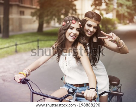 Portrait of funny boho girls on the tandem bicycle - stock photo