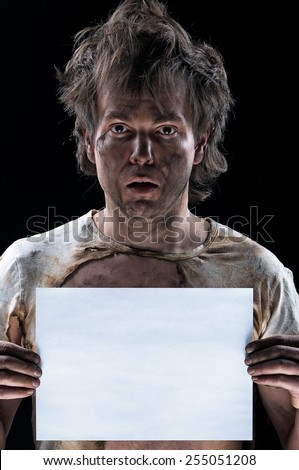 Portrait of funny electrician showing blank placard board over black background - stock photo