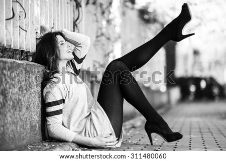 Portrait of funny female model of fashion with high heels sitting on the floor moving her legs - stock photo