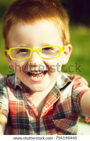 Portrait of funny happy smiling cute little boy with red hair in checkered shirt and yellow glasses sunny day outdoor on blurred natural background, vertical picture
