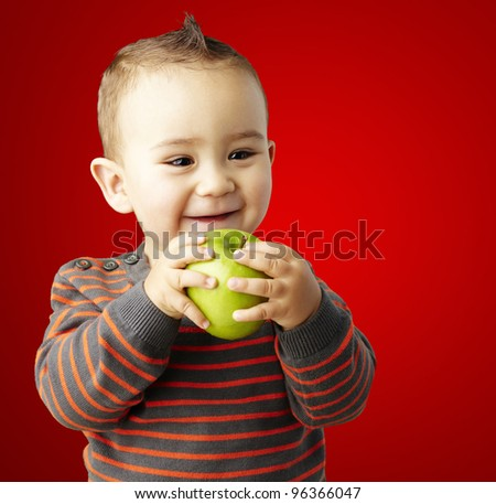 portrait of funny kid holding green apple and smiling over red background