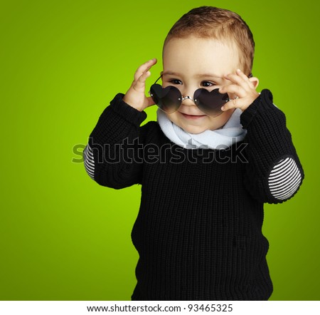 portrait of funny kid wearing heart sunglasses against a green background