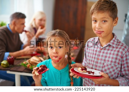 Portrait of funny kids eating sweet pie on background of their parents - stock photo