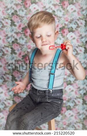 Portrait of funny little boy blowing soap bubbles. Background: floral, soft, pastel  - stock photo