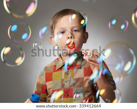 Portrait of funny little boy blowing soap bubbles.happy child - stock photo
