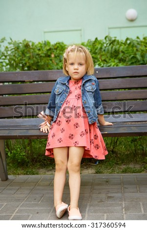 Portrait of funny little child, adorable blonde toddler girl outdoors - stock photo