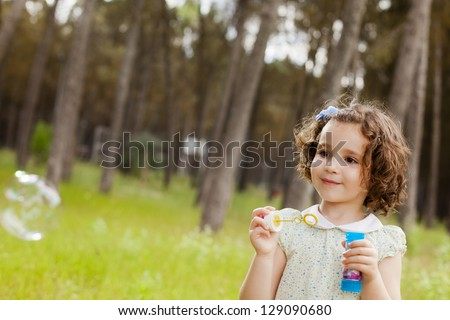 Portrait of funny lovely little girl making soap bubbles. Free space for your own bubbles. - stock photo