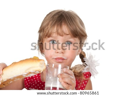 portrait of funny lovely 4 years pretty little girl eat enjoying bite bun, bread with glass of milk, isolated over white background - stock photo