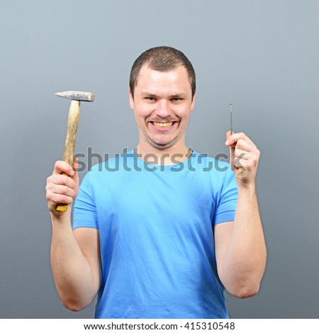 Portrait of funny man holding hammer and nail - stock photo