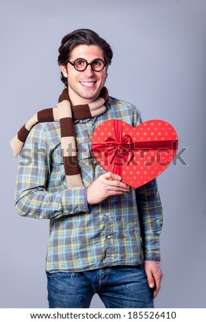 Portrait of funny man in glasses with gift on a gray background.