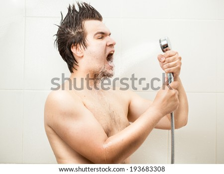 Portrait of funny man singing at shower - stock photo