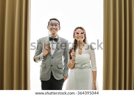 portrait of funny moments of newlywed asian couple on white background with curtain - stock photo