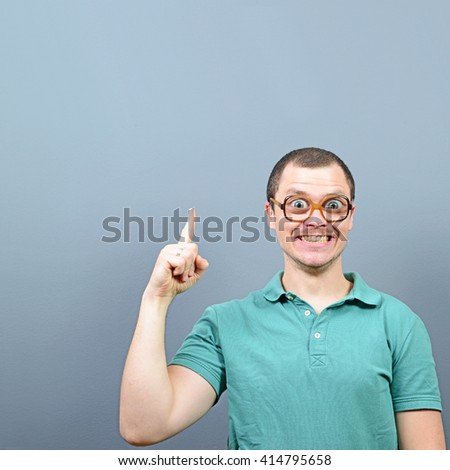 Portrait of funny nerd with big eyes having an idea  and showing at empty space above against gray background - stock photo