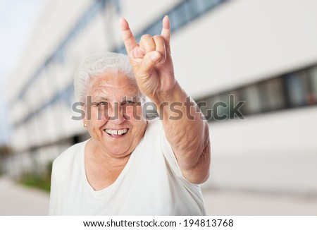 portrait of funny old woman doing a rock and roll symbol - stock photo