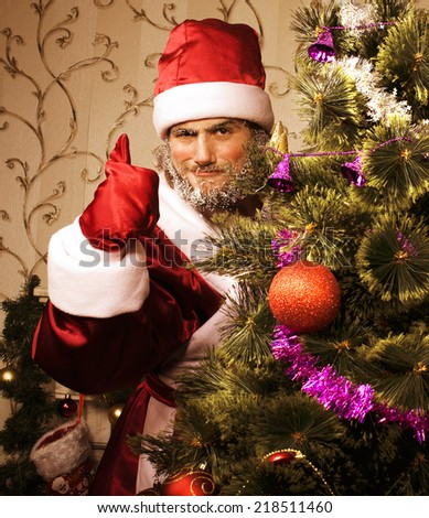 portrait of funny Santa Claus at home with christmass tree - stock photo