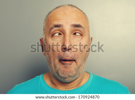 portrait of funny senior man in blue t-shirt over grey background - stock photo