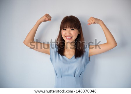 Portrait of funny strong muscle Asian woman smiling wearing blue dress isolated on blue background. Asian female model. - stock photo
