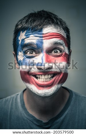 Portrait of funny toothy smiling man with US flag painted on face.