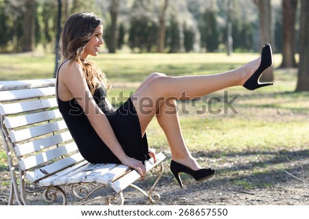 Portrait of funny woman, model of fashion with very long legs, sitting on a bench in an urban park, wearing black dress and high heels - stock photo