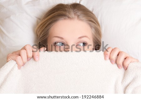 portrait of funny young beautiful woman lying in bed under blanket - stock photo