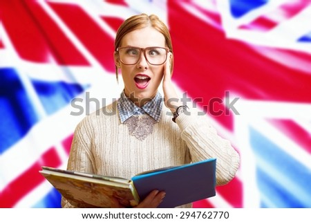 Portrait of funny young pretty female in glasses holding books with the UK flag on the background. Learn English - stock photo