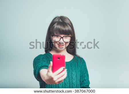 portrait of funny young woman photographed on the phone, hipster isolated on a gray background
