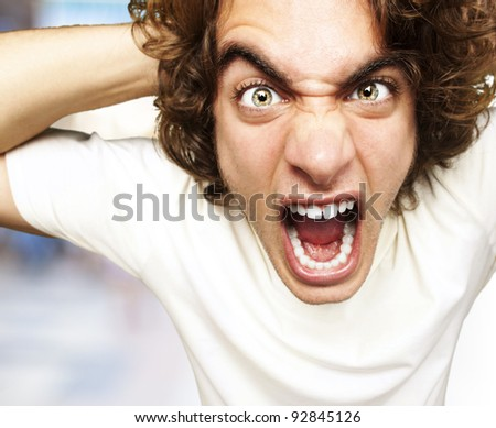 portrait of furious young man shouting against a abstract background - stock photo