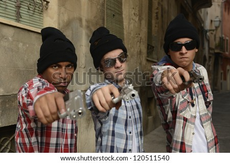 Portrait of gang members with guns on the street - stock photo