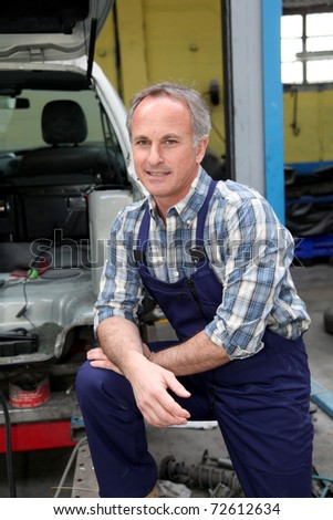 Portrait of garage owner standing by vehicle - stock photo